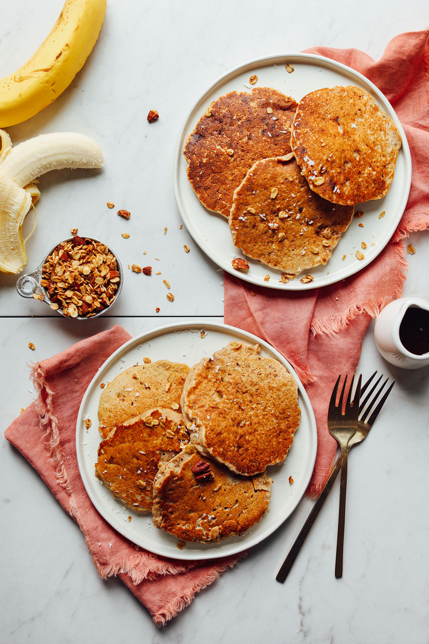 Two plates with gluten-free vegan Banana Pancakes sprinkled with granola