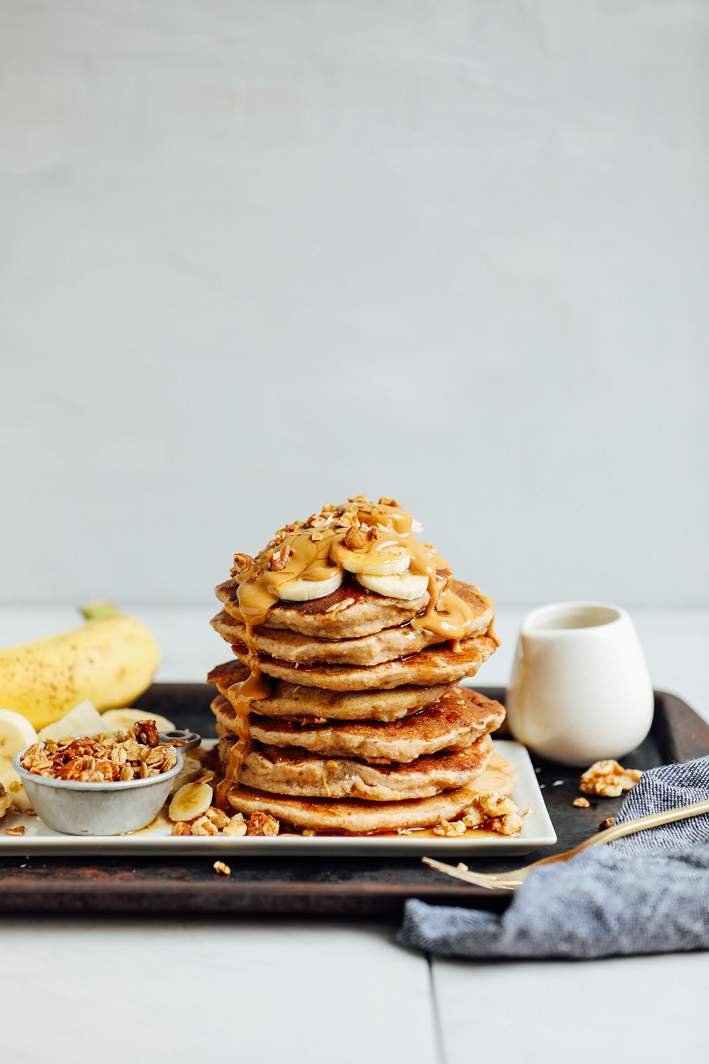 Stack of naturally sweetened gluten-free Banana Pancakes topped with fresh bananas, peanut butter, and walnuts