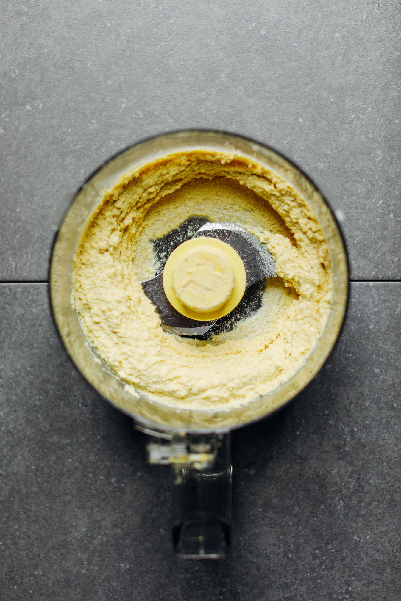 Food processor with freshly blended vegan Macadamia Nut Herb Cheese