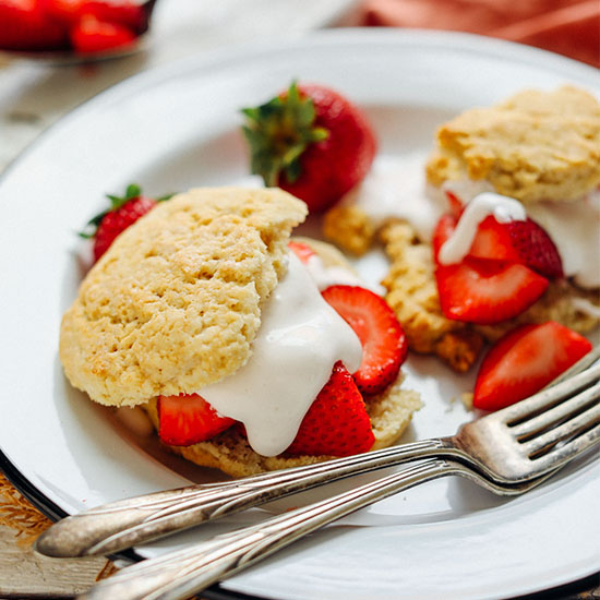 Plate of Two Vegan GF Shortcake Biscuits filled with strawberries and coconut whipped cream
