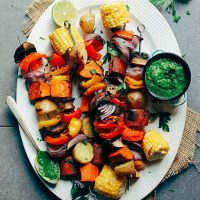 Platter of Grilled Veggie Skewers with a small dish of Chimichurri sauce
