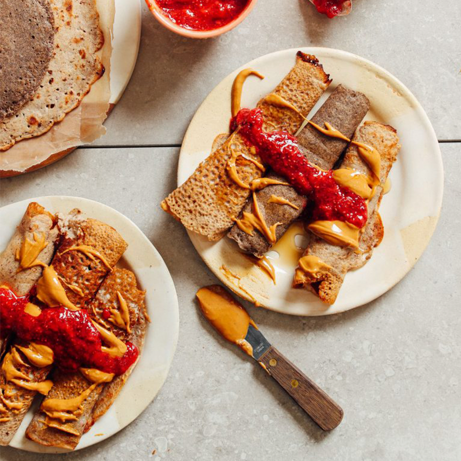Plates of homemade Buckwheat Crepes topped with berry compote and peanut butter
