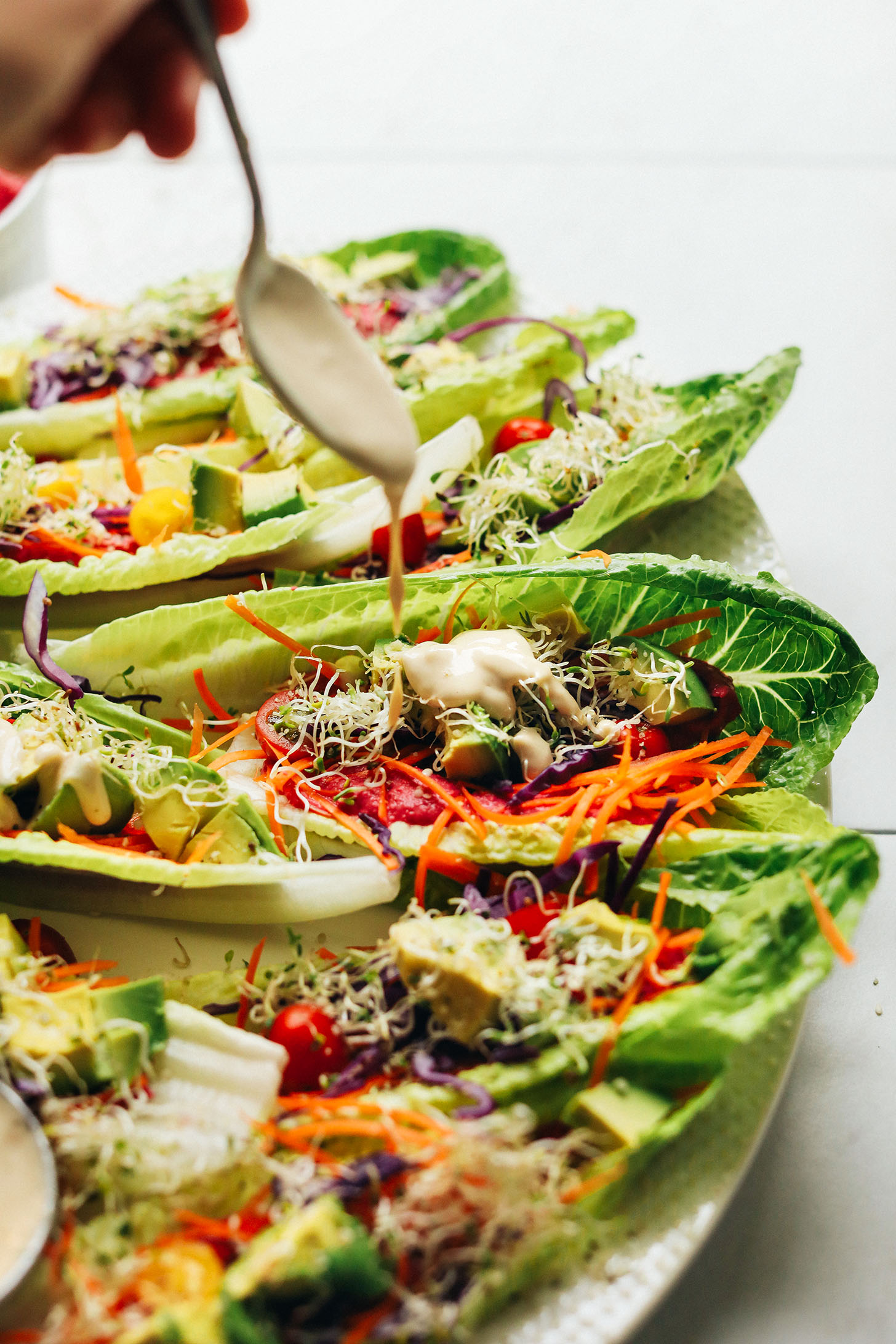 Drizzling tahini dressing onto Raw Romaine Taco Boats for a refreshing vegan meal