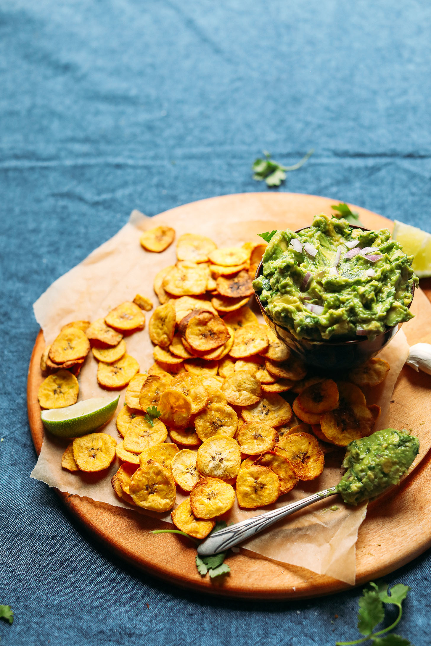 Wood cutting board with homemade Baked Plantain Chips and a bowl of Garlicky Guacamole