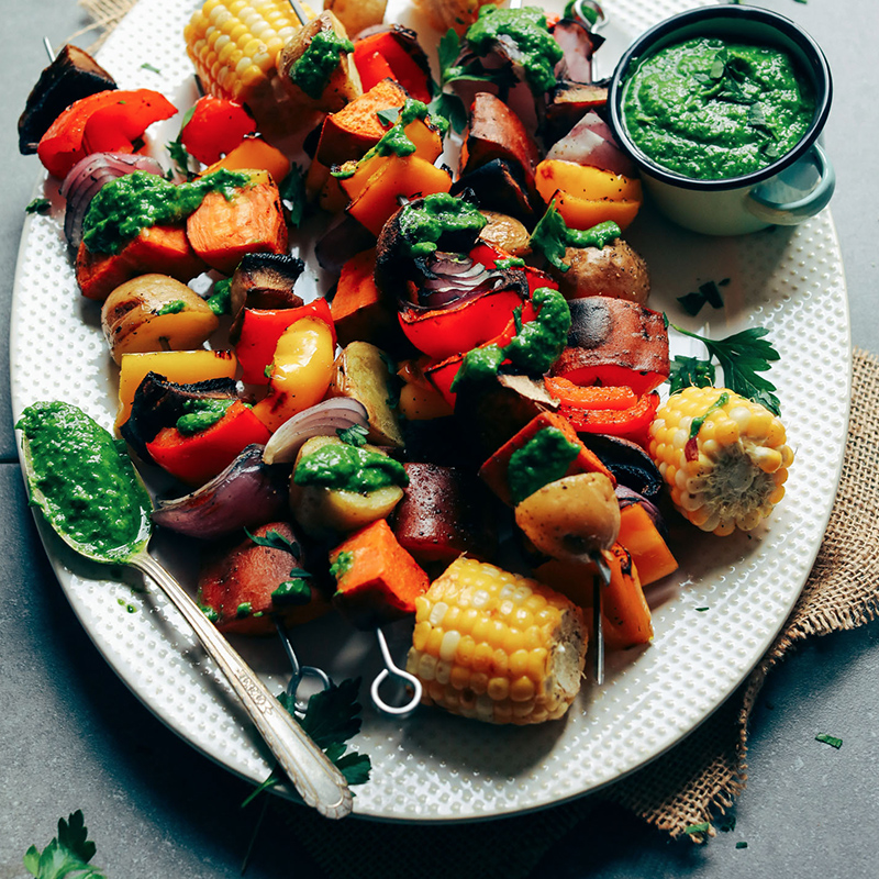 Platter of Grilled Veggie Skewers topped with homemade Chimichurri