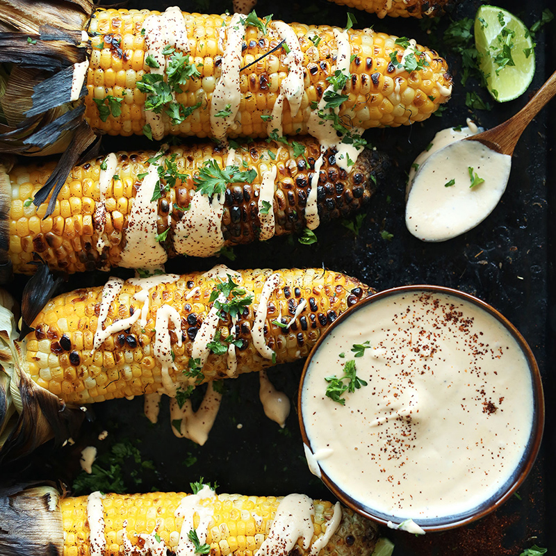 Ears of grilled corn next to a bowl of sriracha aioli