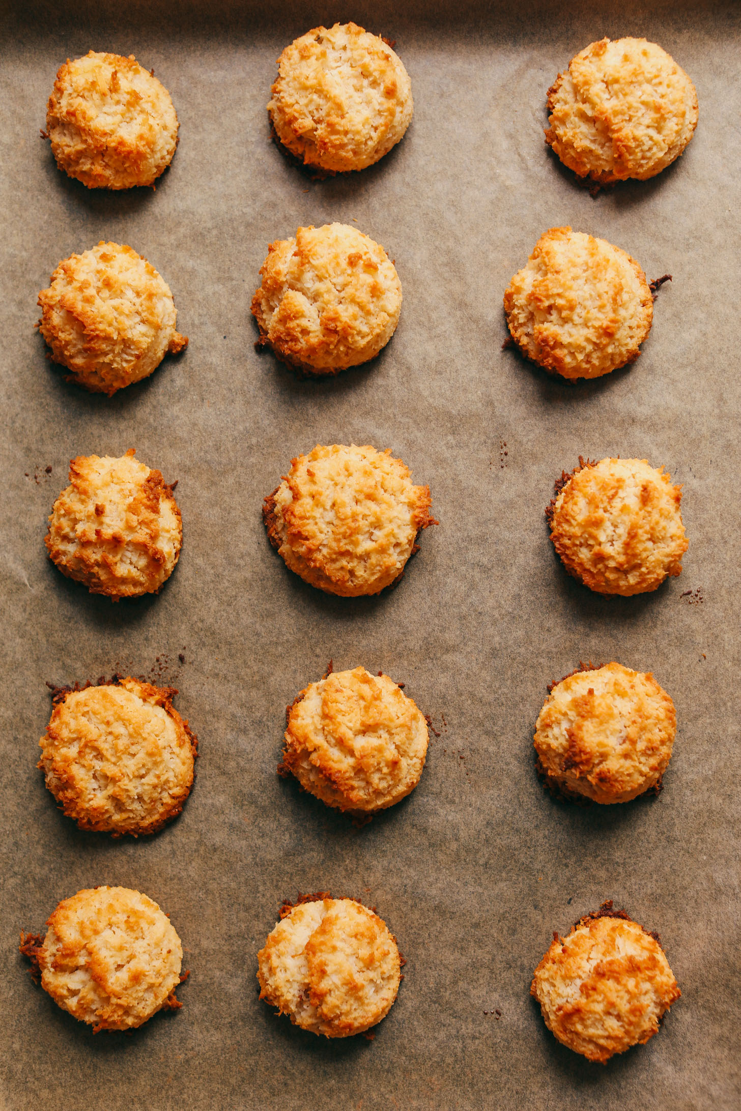 Freshly baked Crispy Vegan Macaroons on a parchment-lined baking sheet