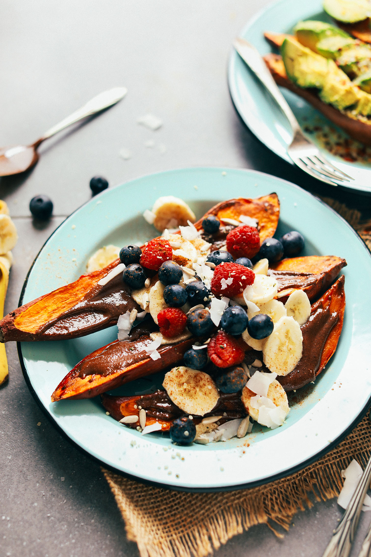 Plate with baked sweet potato topped with vegan melted chocolate, banana, fresh berries, and coconut flakes