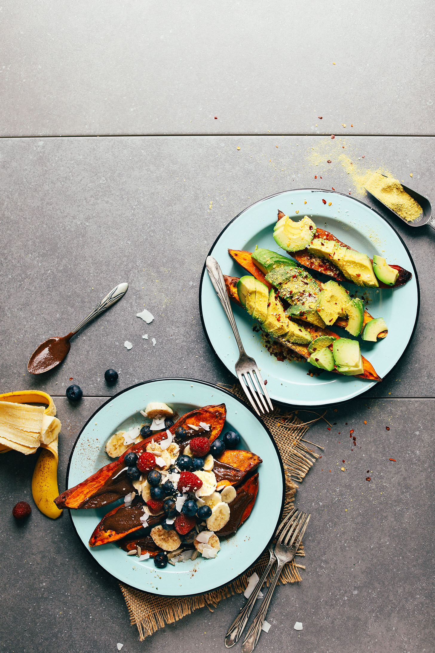 A savory plate of baked sweet potato with avocado, chili flakes, nutritional yeast, and salt and a sweet plate of baked sweet potato with fresh fruit, chocolate, and coconut