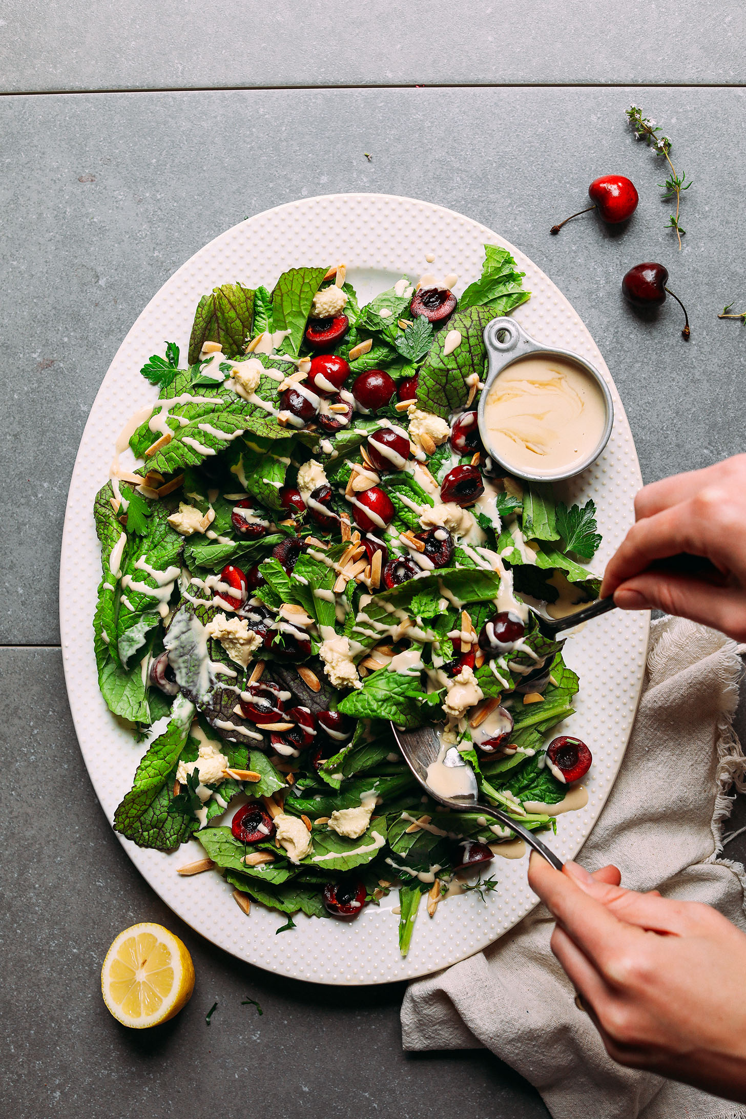 Grabbing a serving of our healthy Mustard Green Salad with Cherries, Toasted Almonds, Nut Cheese, and Tahini Dressing
