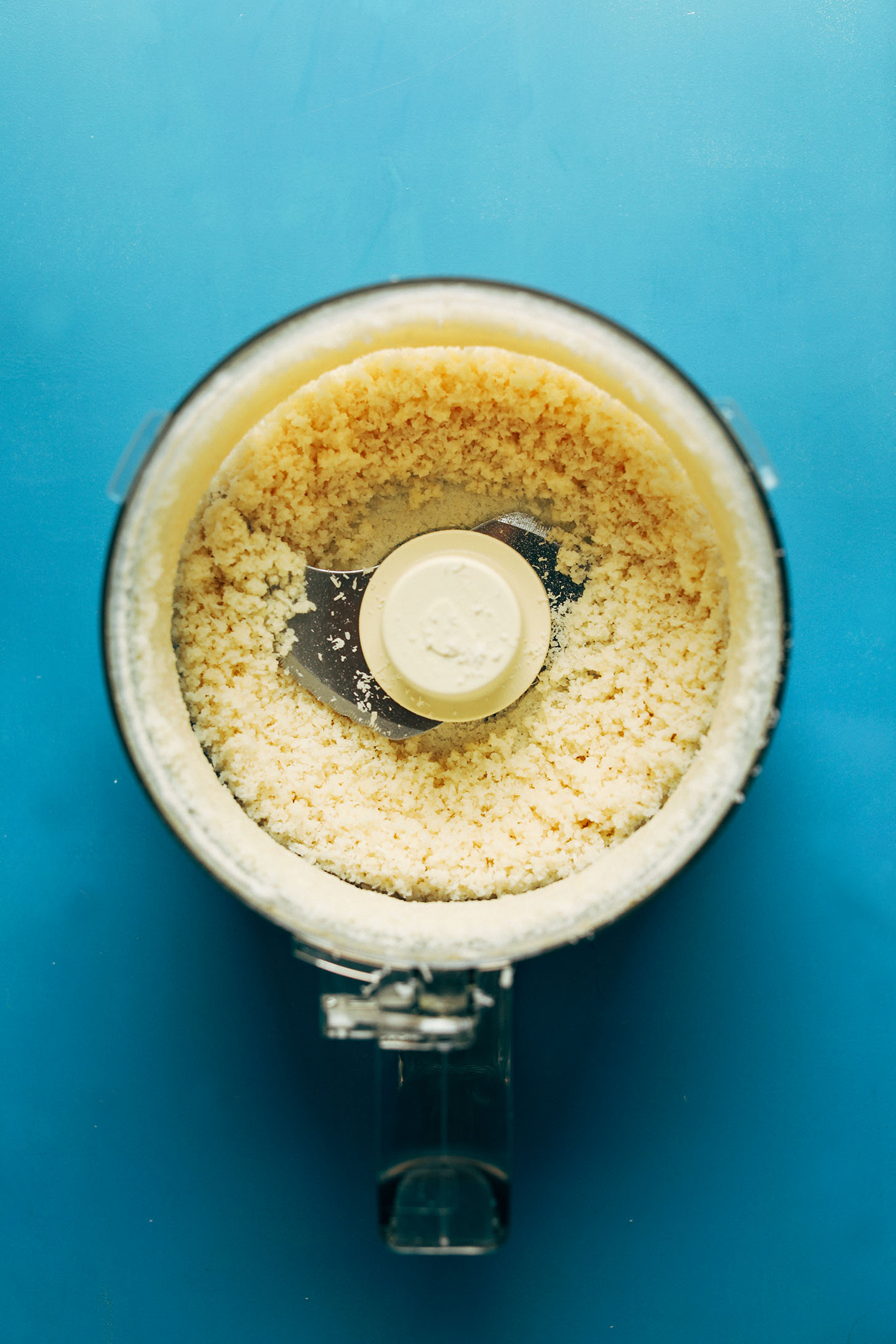 Food processor with a batch of partially-made coconut butter