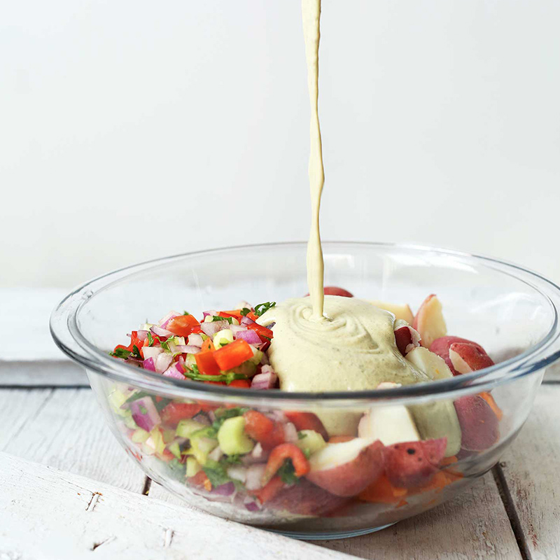 Pouring cashew dressing onto a bowl of our Vegan Potato Salad recipe