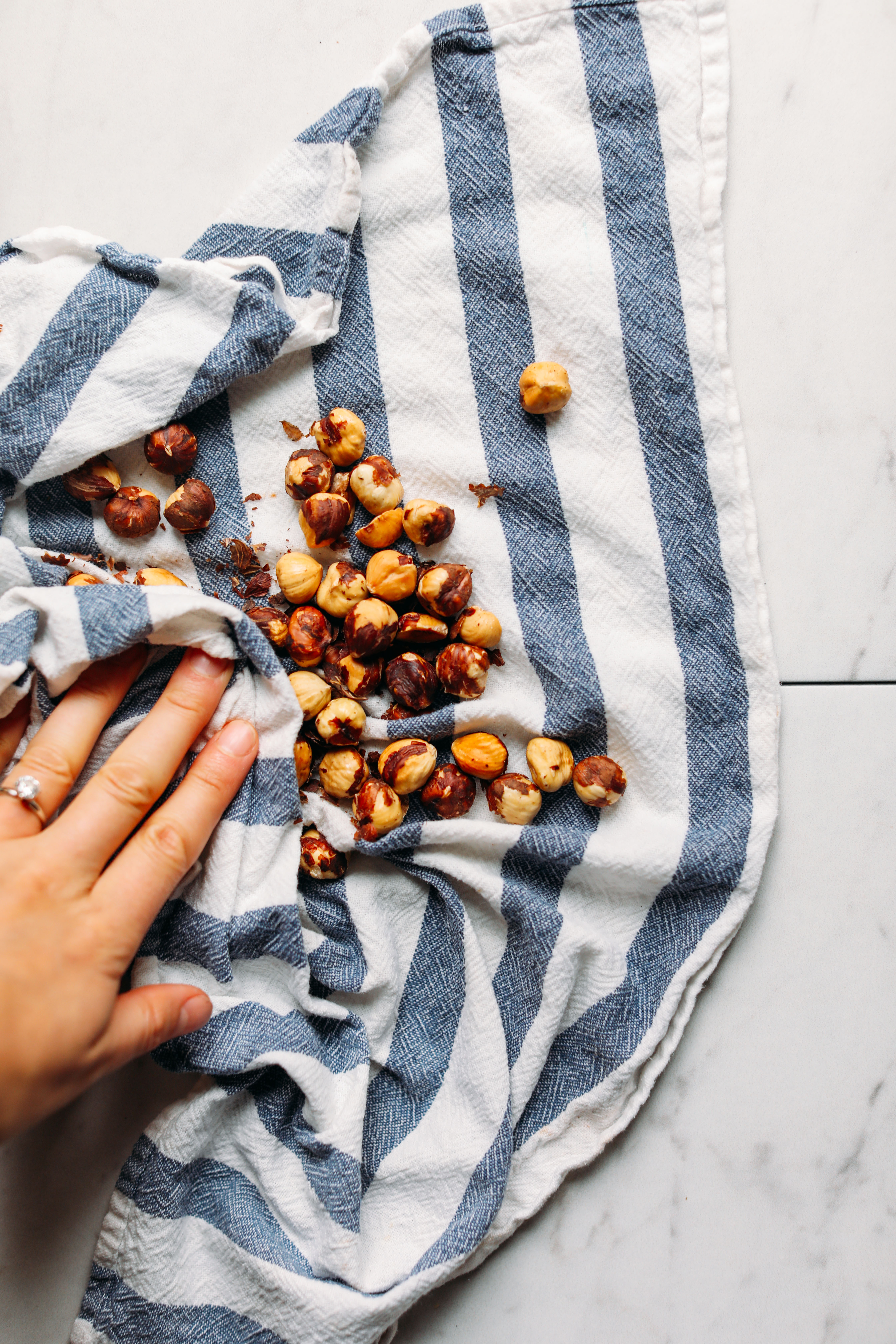 Using a dish towel to remove the skins of roasted hazelnuts