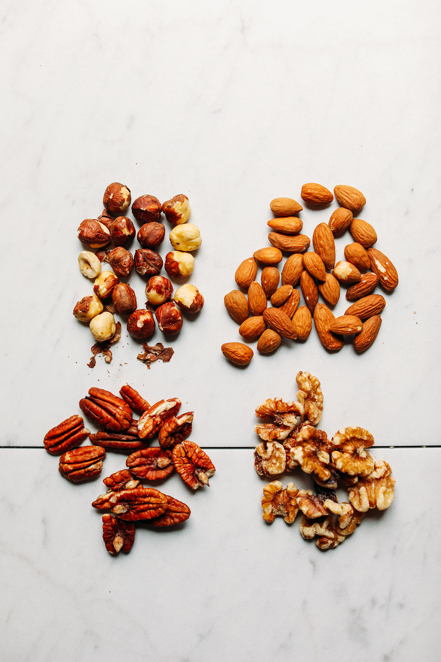 Walnuts, pecans, almonds, and hazelnuts on a marble background