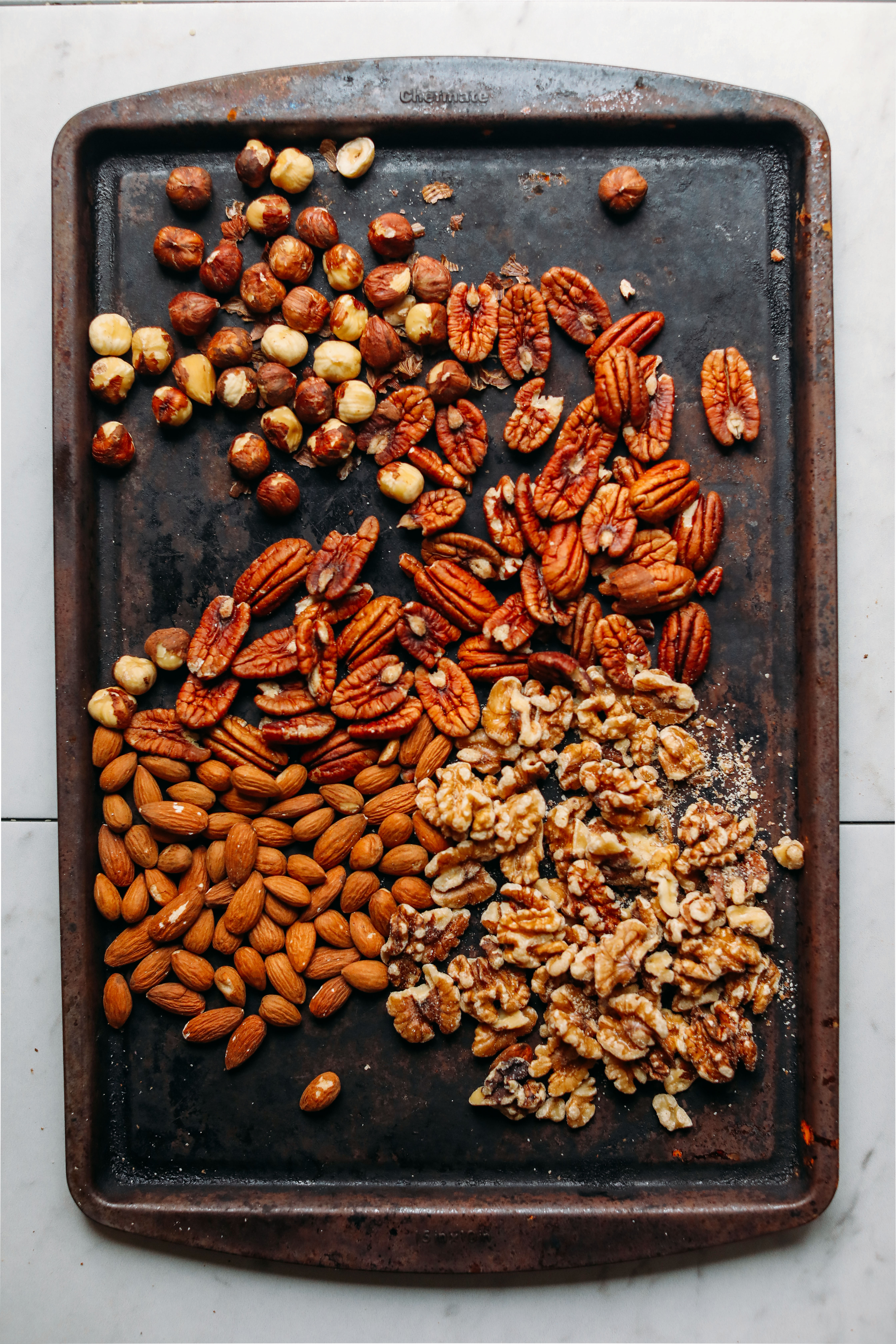 Baking sheet filled with nuts for making homemade nut butter