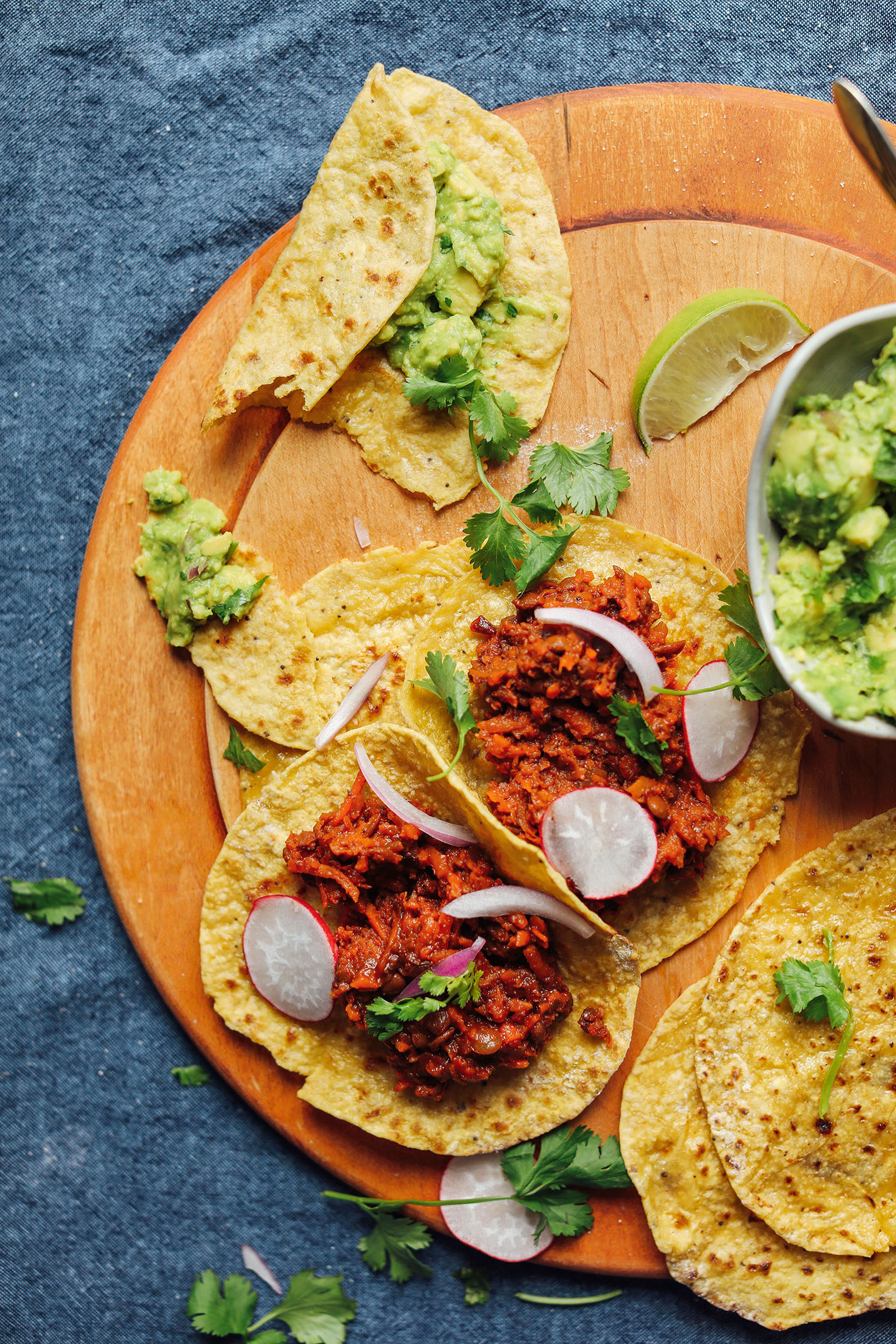Cutting board with grain-free Plantain Tortillas filled with Barbacoa Lentils and guacamole