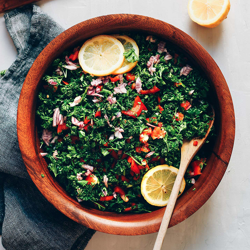 Wooden spoon resting in a bowl of our Grain-Free Tabbouleh Salad
