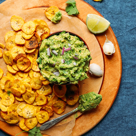 Scooping up Garlicky Guacamole with a crispy homemade Plantain Chip