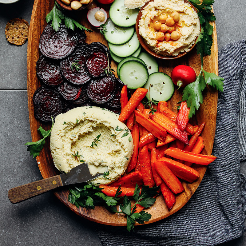 Wood tray of Macadamia Nut Herb Cheese and vegetables