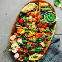 Wood platter filled with Roasted Vegetable Salad drizzled with chimichurri