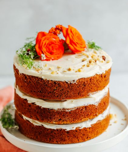 The best three-layer Vegan Gluten-Free Carrot Cake decorated with flowers and chopped nuts