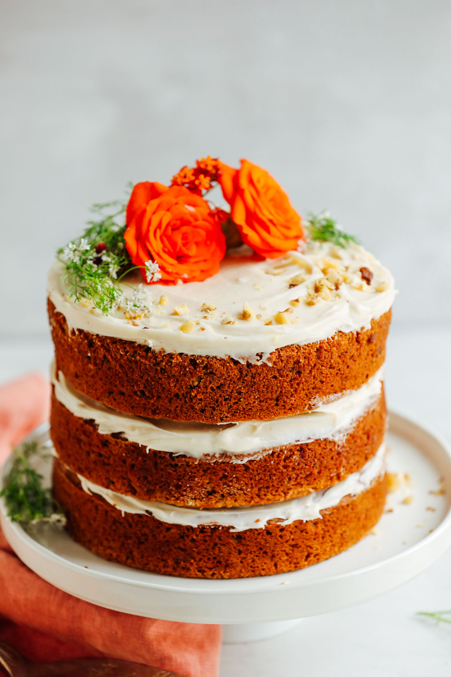 Three-layer Vegan Gluten-Free Carrot Cake decorated with flowers and chopped nuts