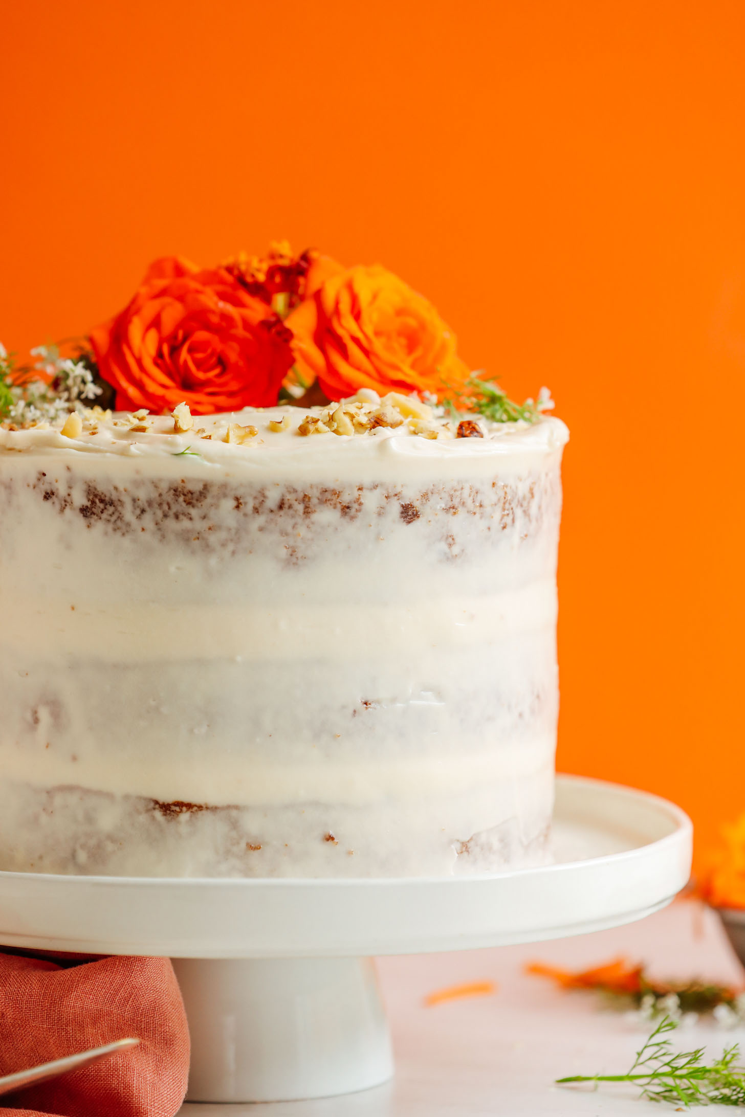 Lightly frosted Vegan Gluten-Free Carrot Cake decorated with fresh flowers and chopped nuts