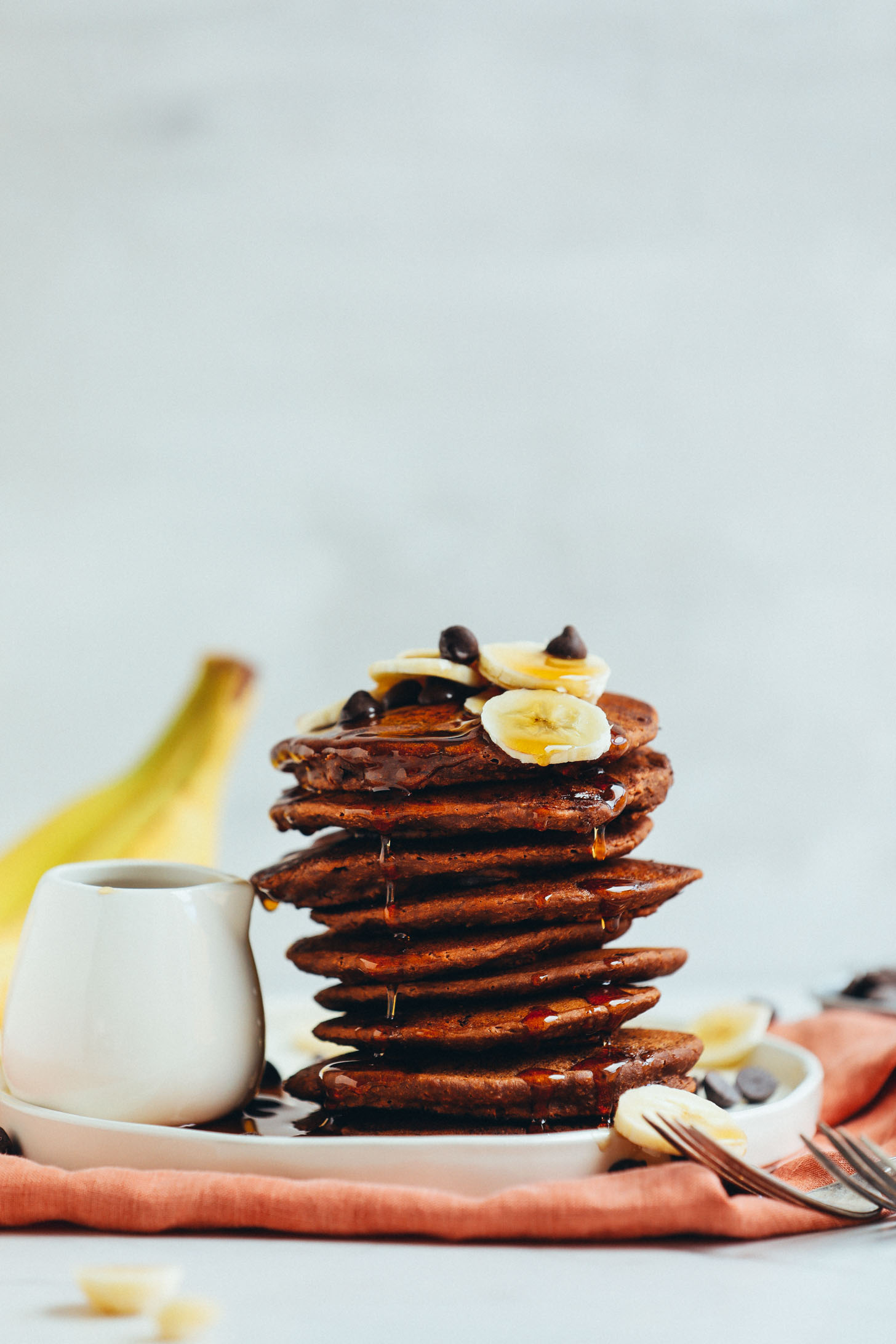 A stack of fluffy Vegan Chocolate Chocolate Chip Pancakes drizzled with syrup