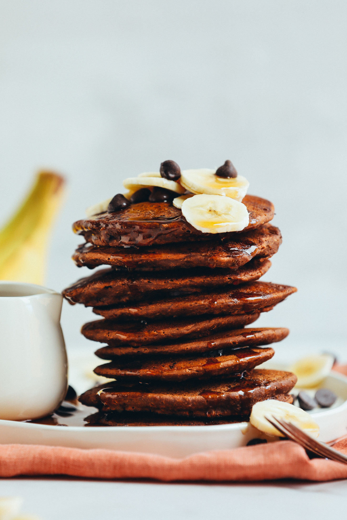 Stack of Amazing Vegan Chocolate Chocolate Chip Pancakes topped with fresh banana