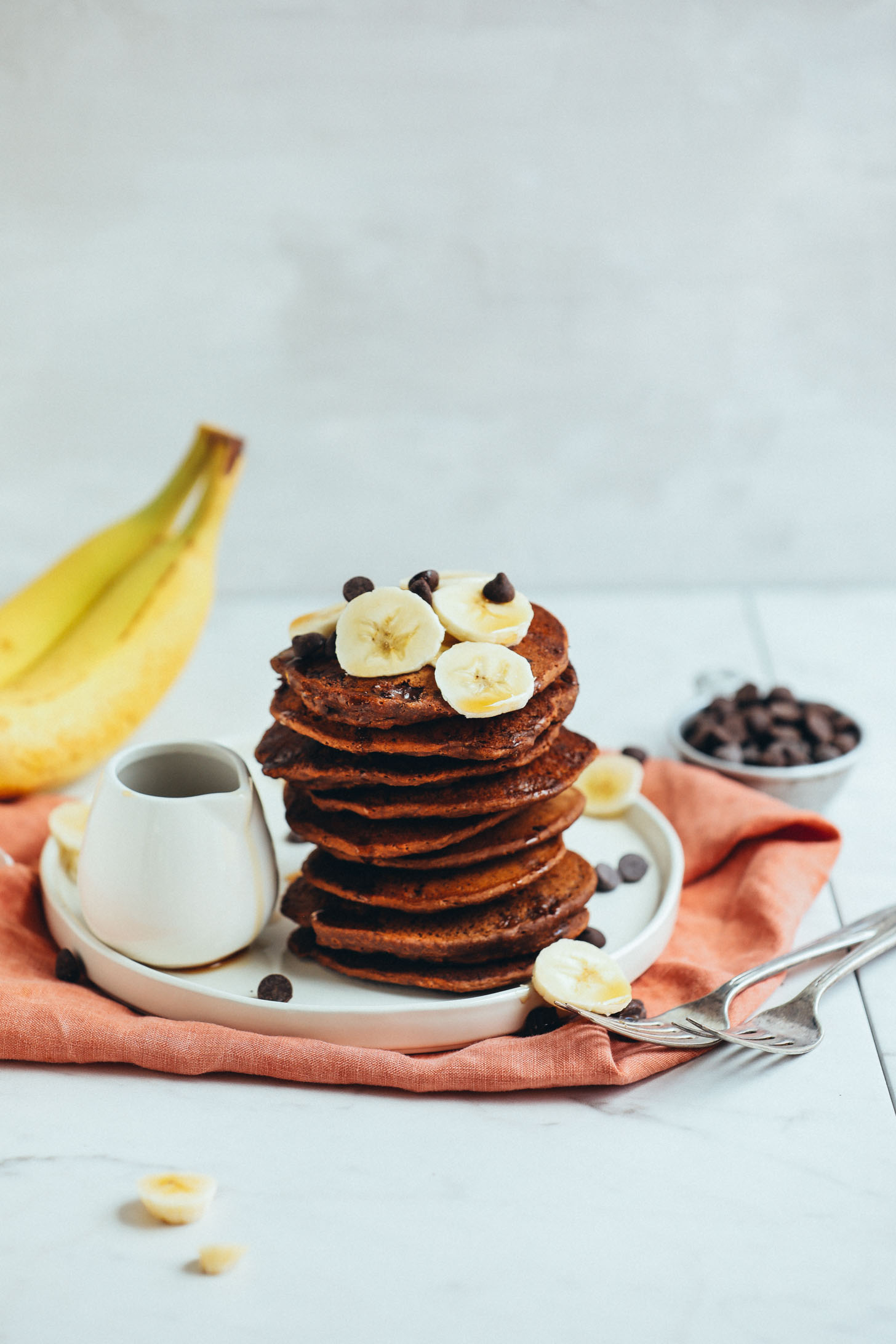 Stack of Vegan Chocolate Chip Pancakes with banana and a side of syrup