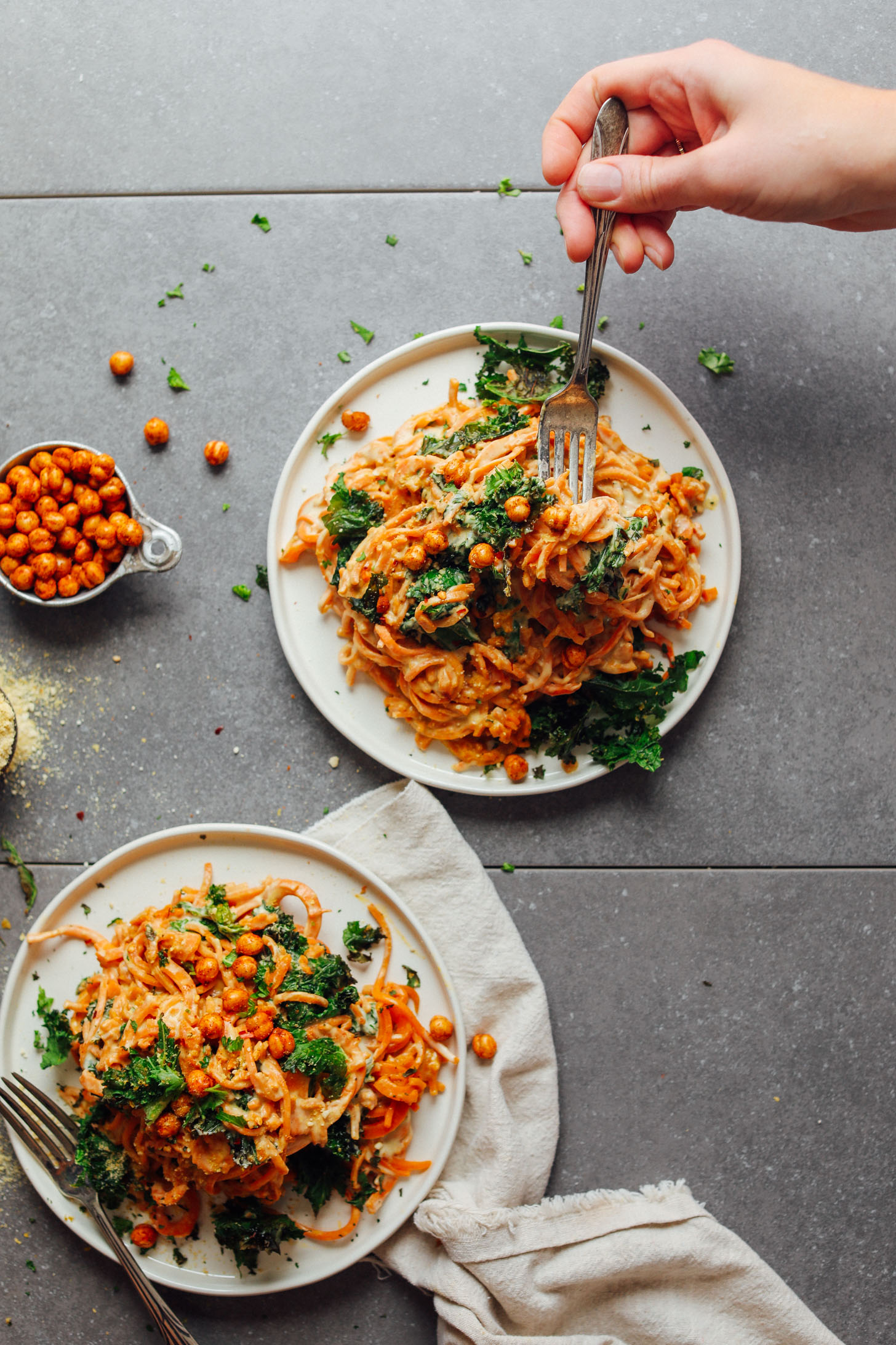 Two dinner plates with large servings of Garlicky Sweet Potato Pasta with Crispy Kale