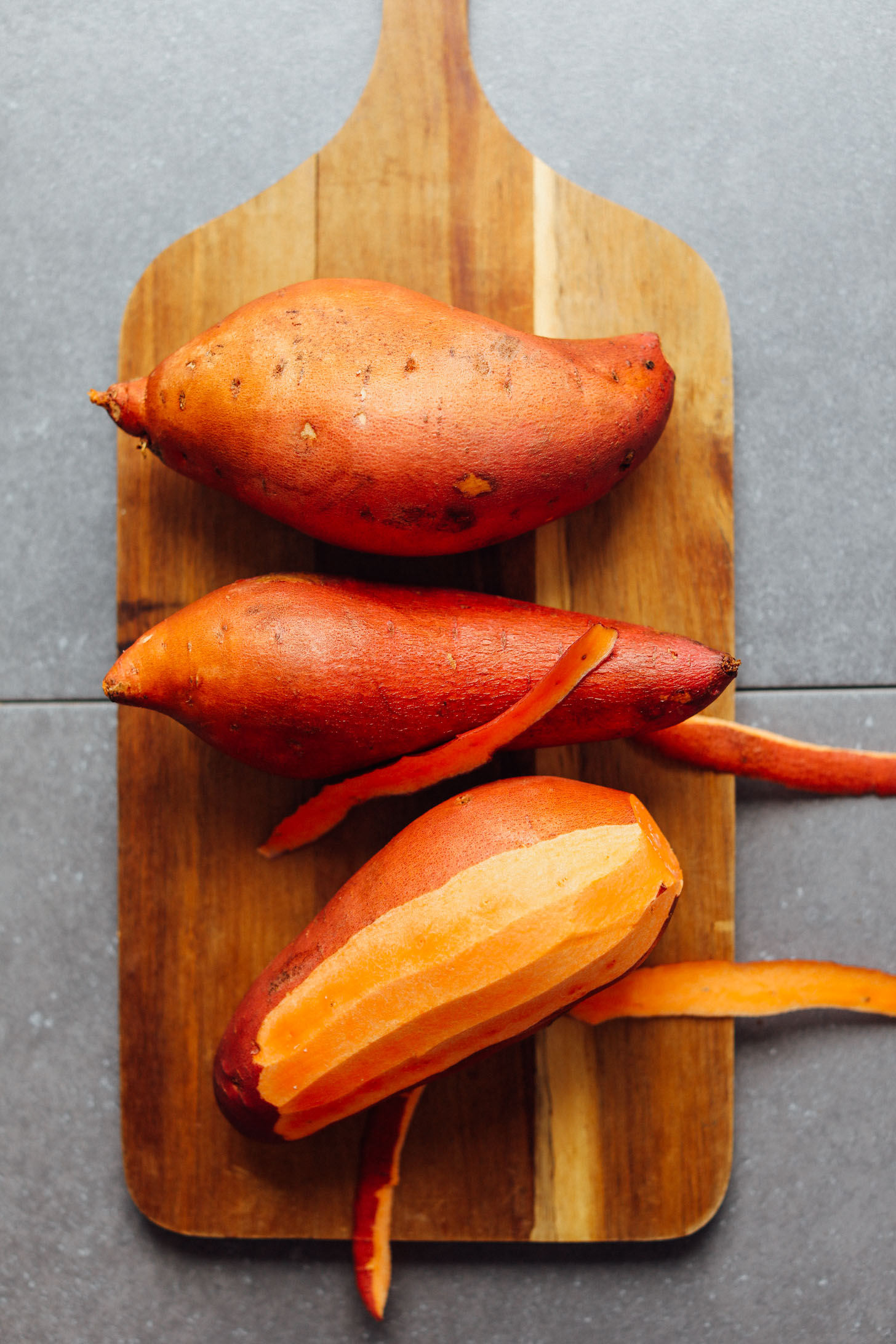 Wood cutting board with sweet potatoes, one of which is partially peeled