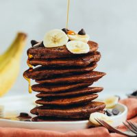 Drizzling syrup onto a stack of Chocolate Chocolate Chip Pancakes topped with sliced banana