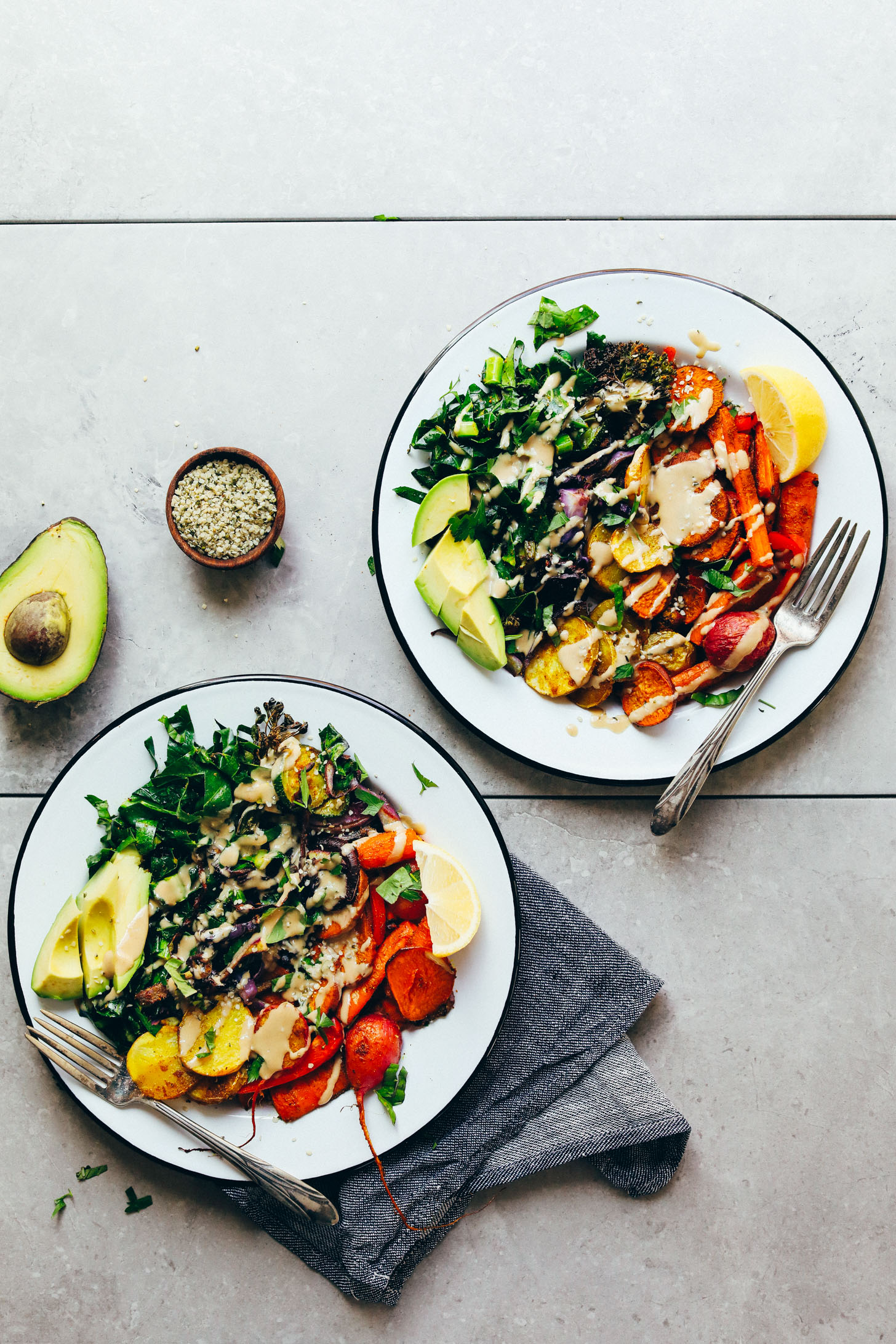 Two big dinner bowls full of Roasted Rainbow Vegetables, avocado, hemp seeds, and tahini dressing