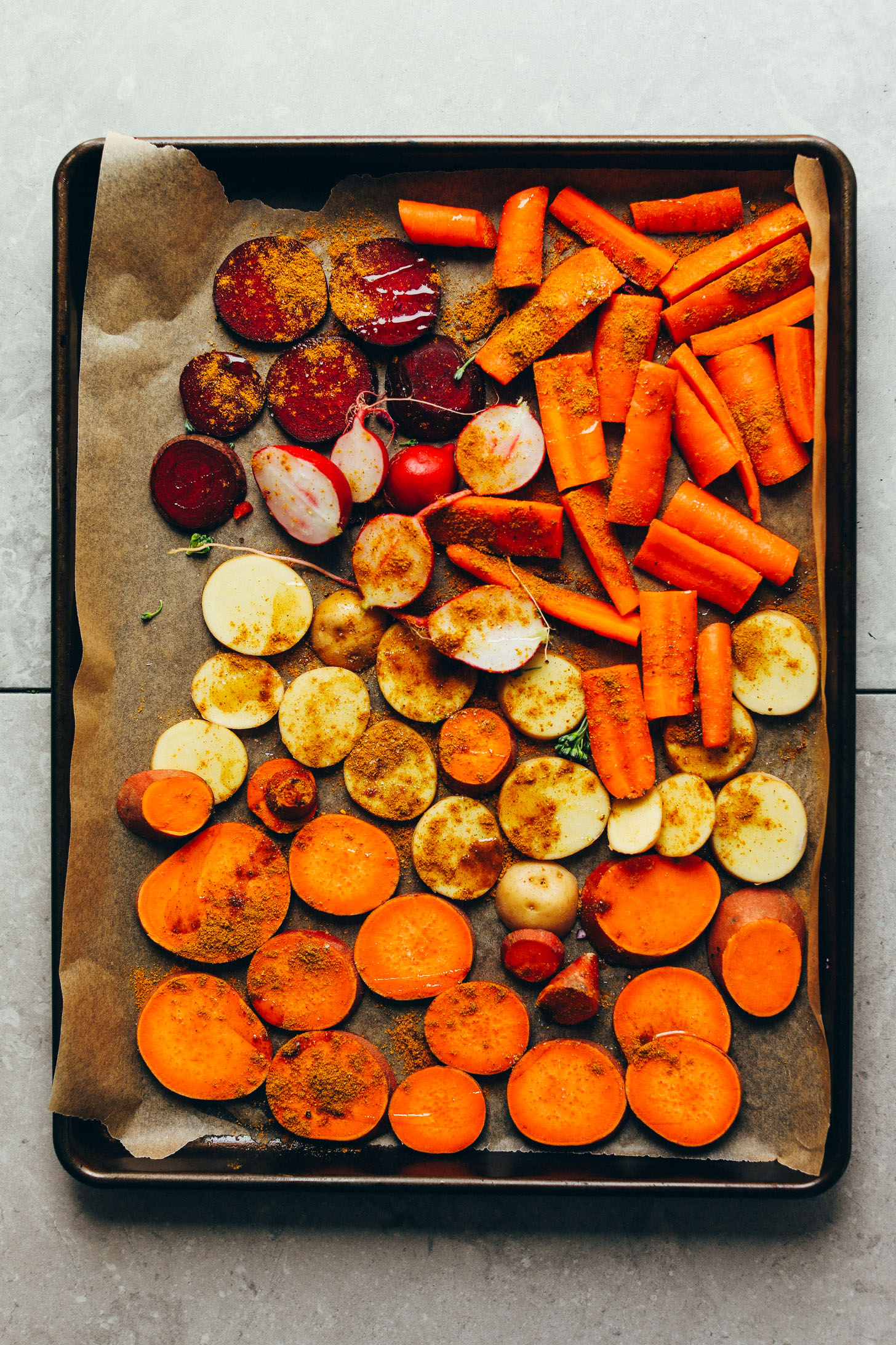 Parchment-lined baking sheet filled with carrots, beets, radish, and sweet potato for roasting
