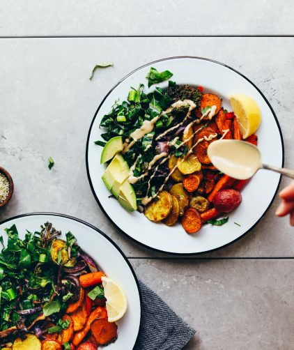 Using a spoon to drizzle tahini dressing onto a gluten-free vegan Roasted Rainbow Vegetable Bowl