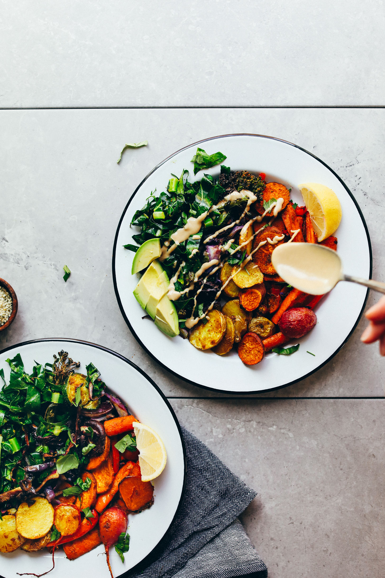 Drizzling tahini dressing onto a nourishing, delicious Roasted Rainbow Vegetable Bowl for a healthy plant-based meal