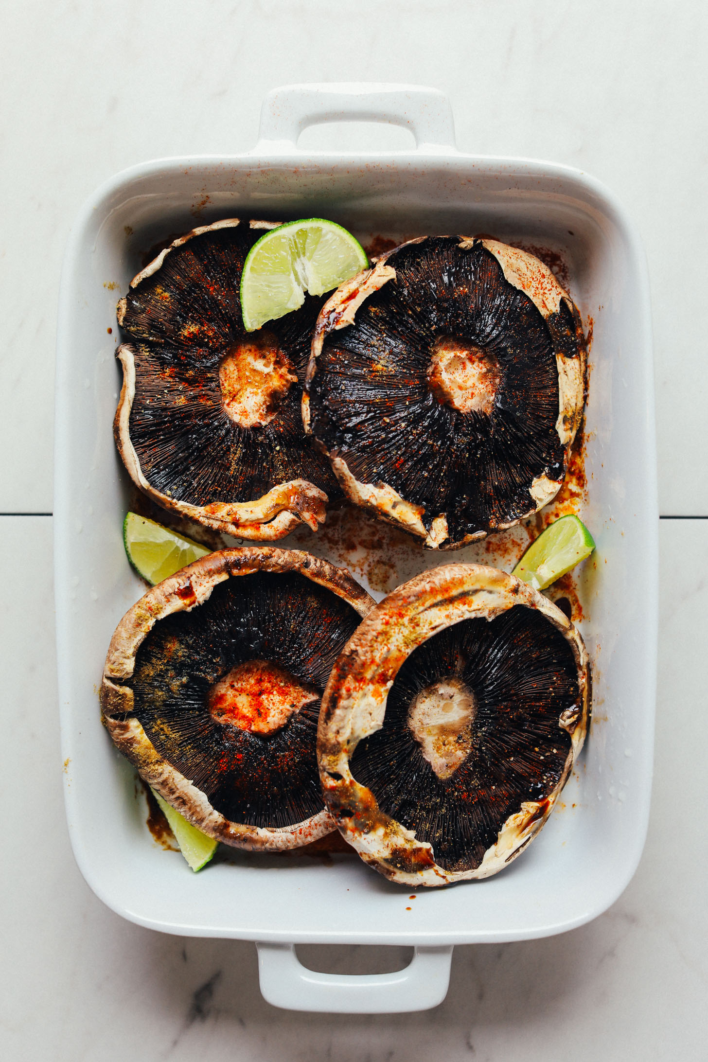 Ceramic baking dish with four portobello mushrooms, spices, and fresh lime wedges
