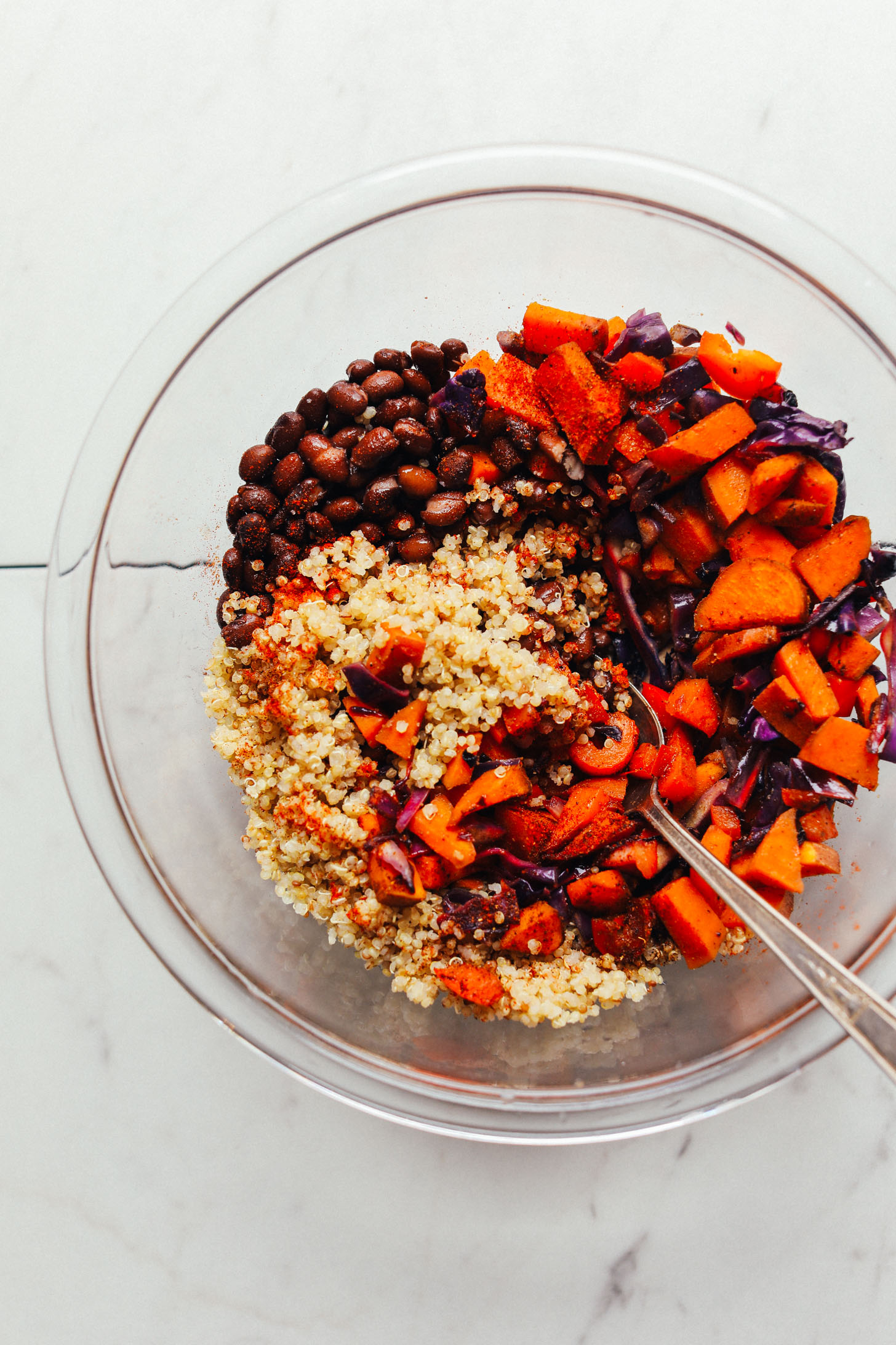 Mixing bowl with quinoa, black beans, sweet potatoes, cabbage, red bell pepper, and spices for filling portobello mushrooms