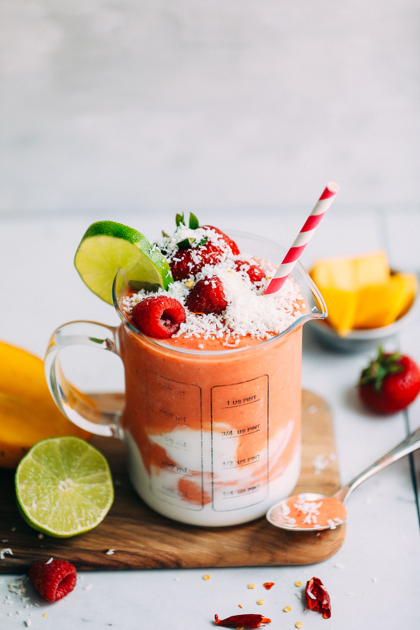 Glass serving jar filled with banana-free Gingery Mango & Berry Smoothie