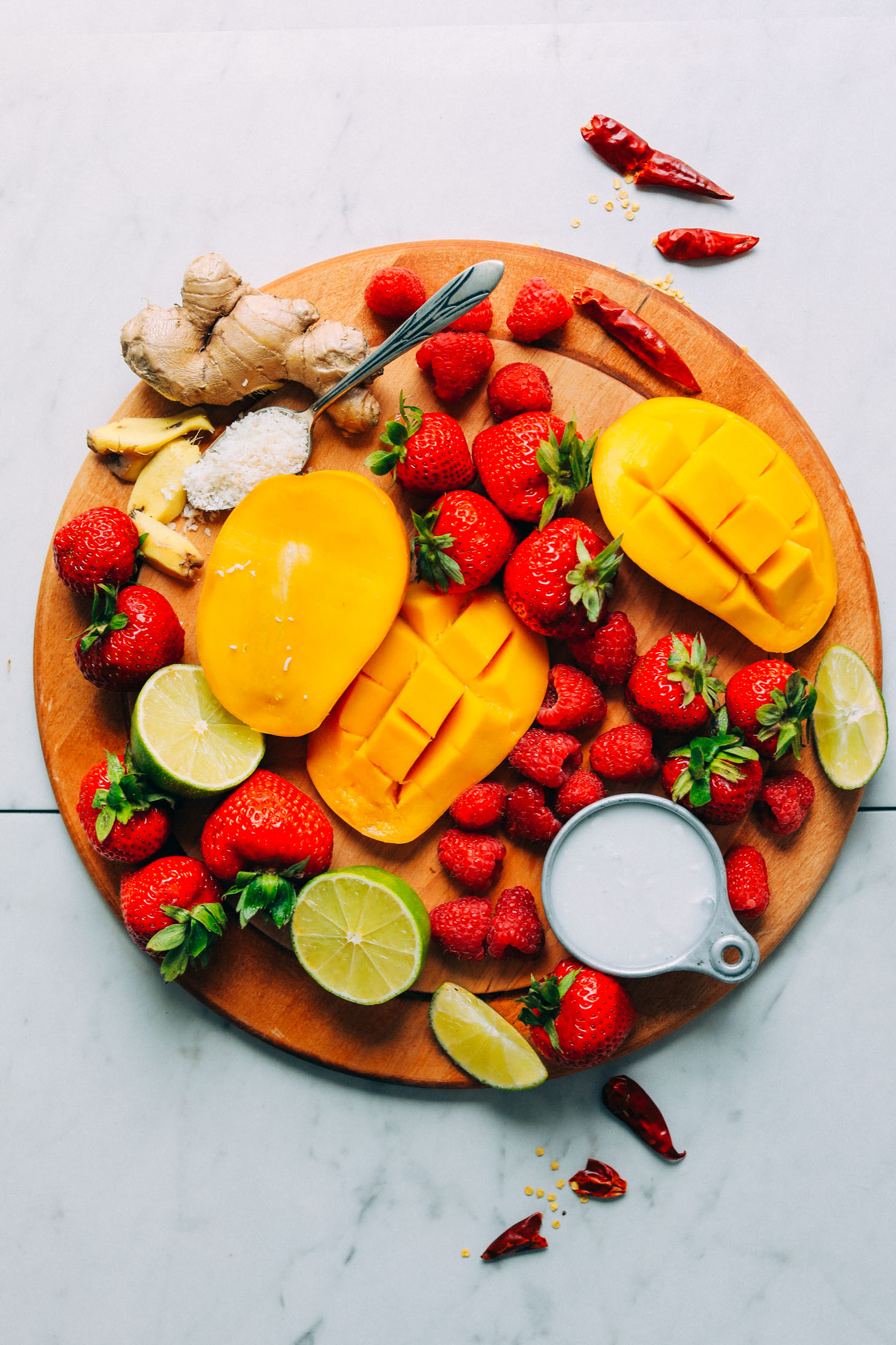 Wood cutting board with fresh fruit for making a vegan Gingery Mango & Berry Smoothie