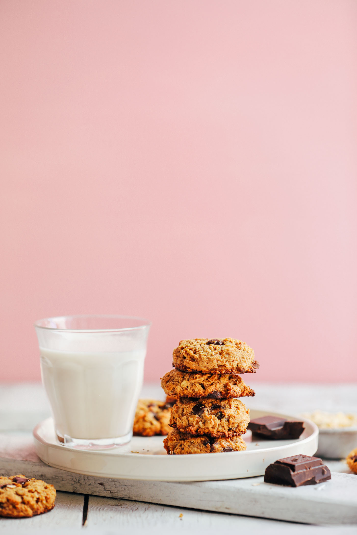 A stack of healthy Gluten-Free Oatmeal Chocolate Chip Cookies alongside a glass of dairy-free milk