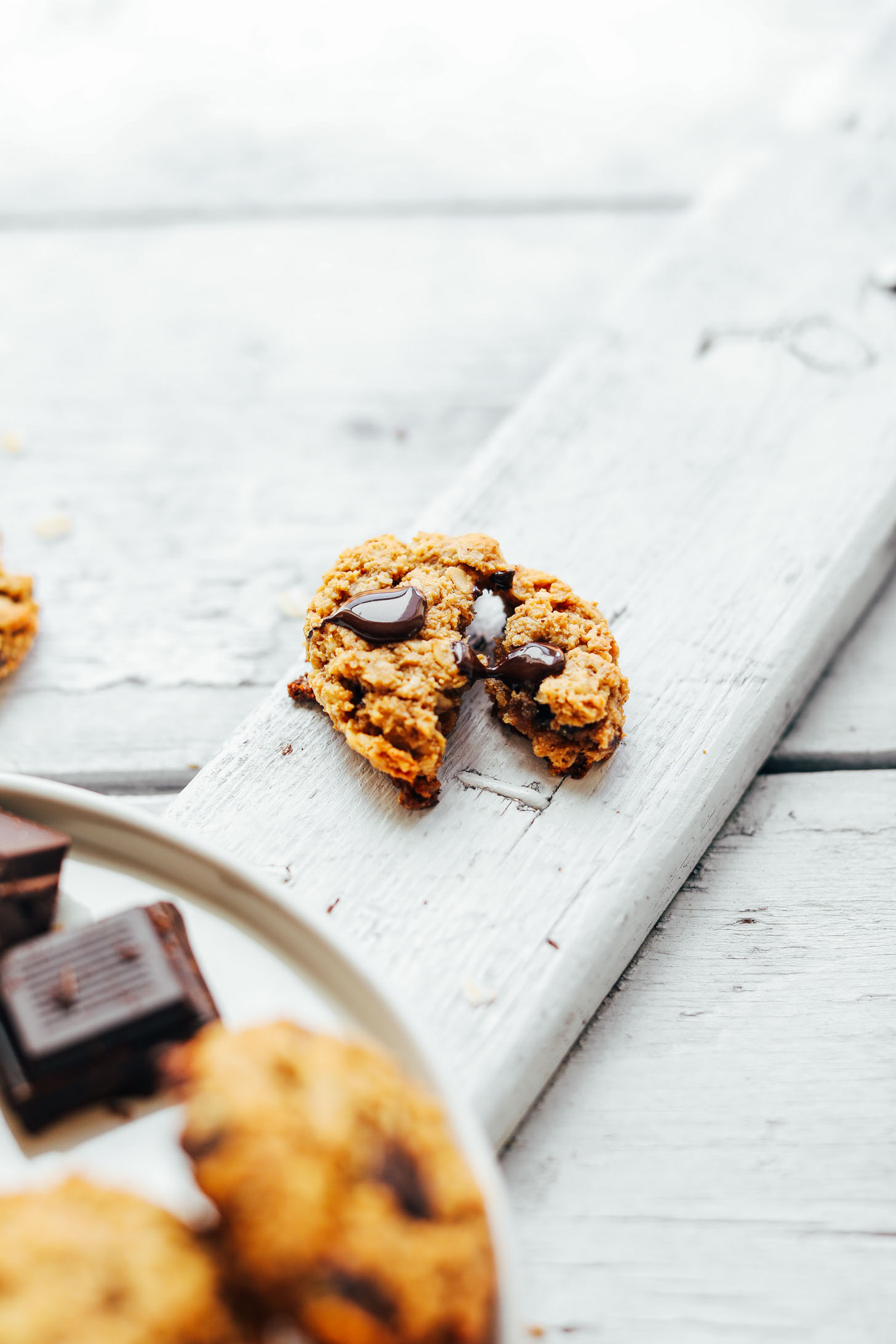 Breaking apart a warm Gluten-Free Oatmeal Chocolate Chip Cookie