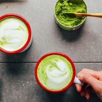 Container of matcha and two mugs of our Vegan Matcha Latte recipe