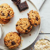 Oats, dark chocolate, and a plate of Healthy Oatmeal Chocolate Chip Cookies