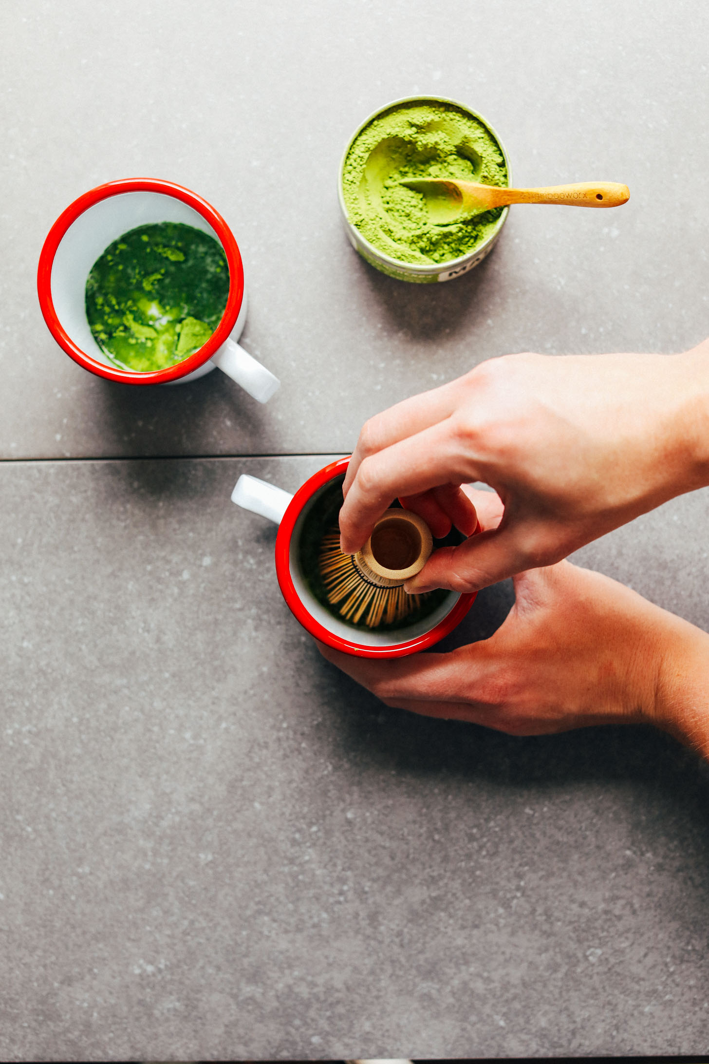 Using a bamboo whisk to stir together matcha, sweetener, and a bit of nut milk