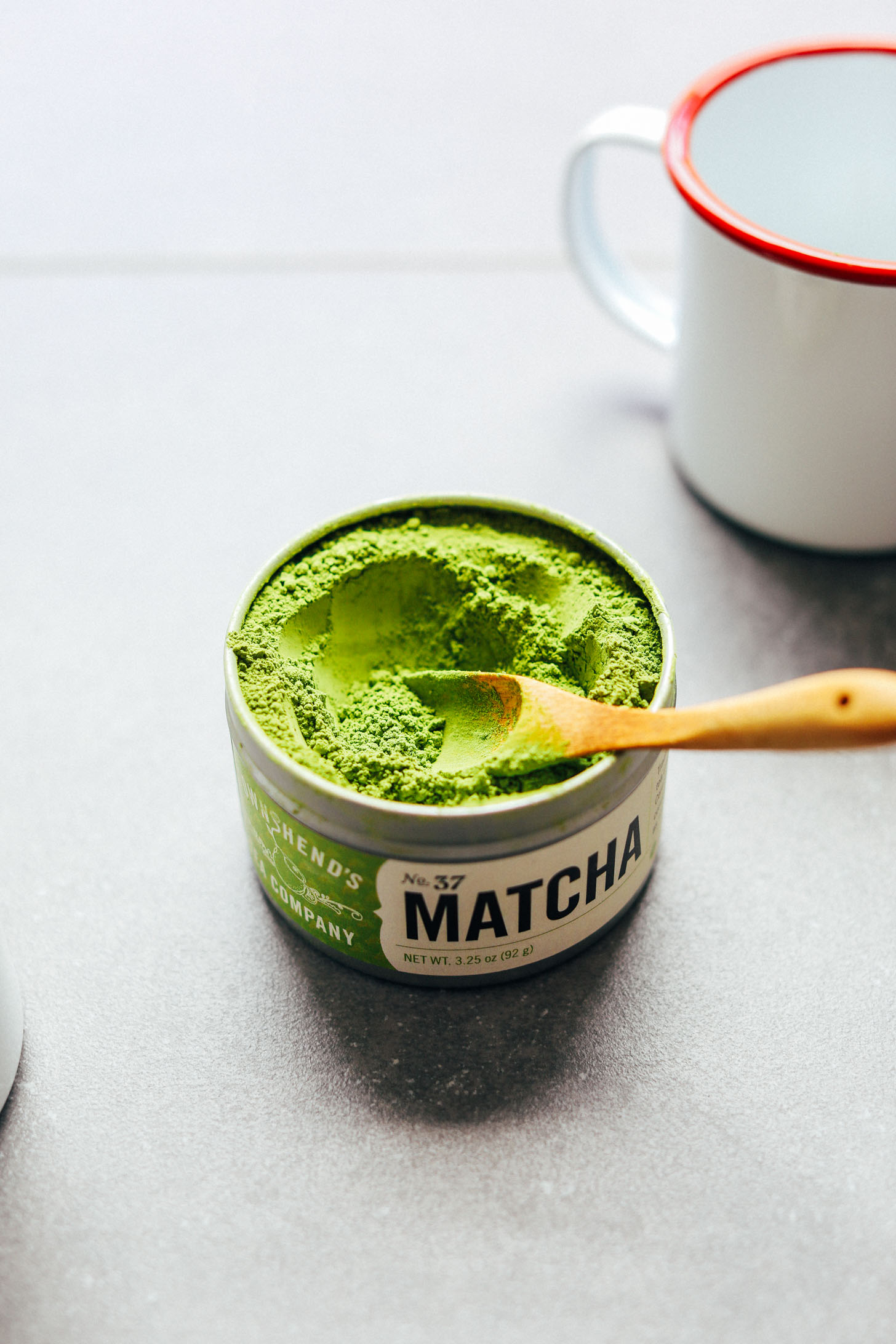 Using a small wooden spoon to grab a scoop of matcha powder for making the Best Matcha Latte