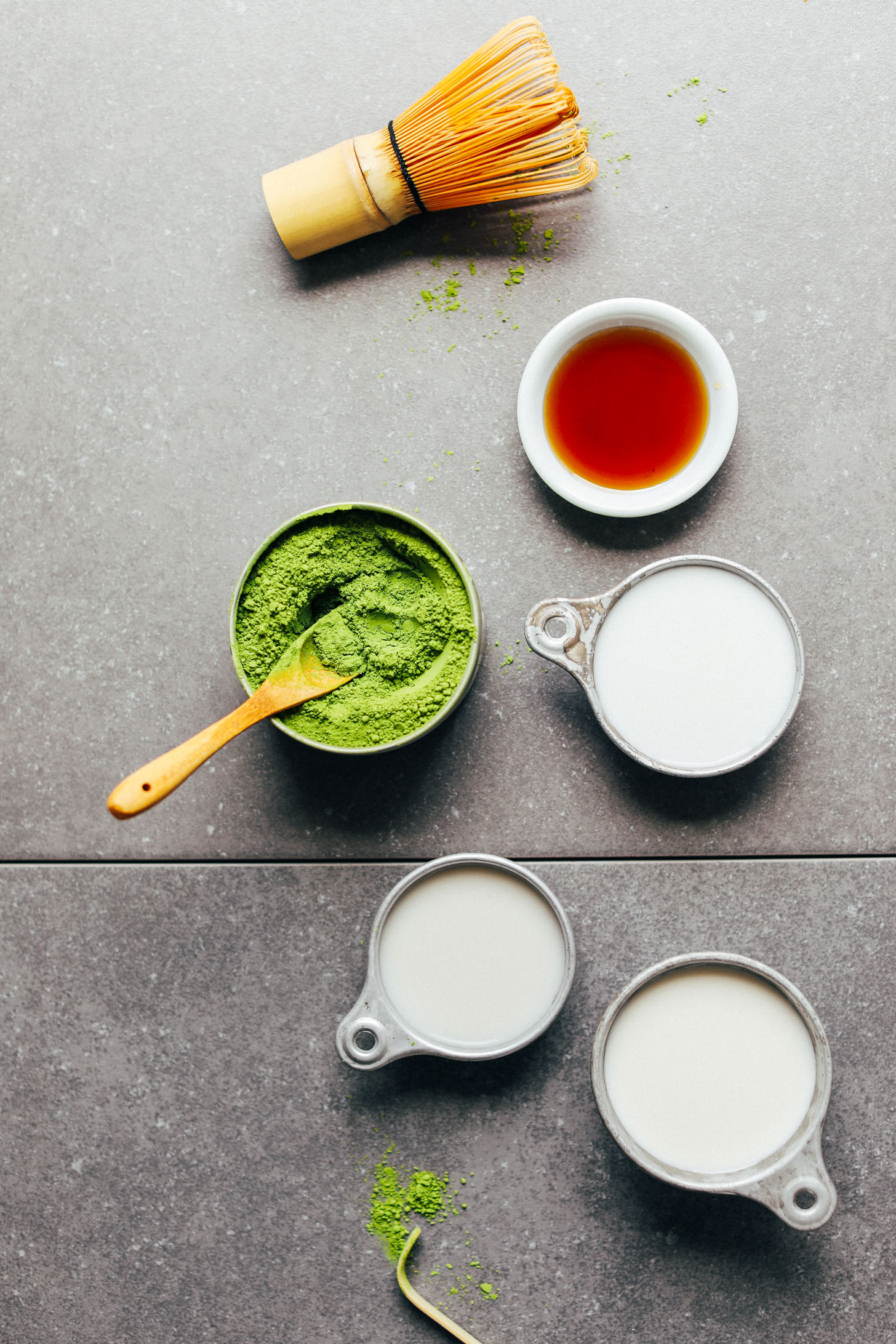 Bamboo whisk, matcha, maple syrup, and nut milks for making the best Matcha Latte
