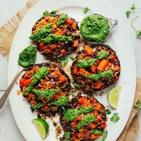 Platter of Vegetable Quinoa Stuffed Portobello Mushrooms with a measuring cup of chimichurri