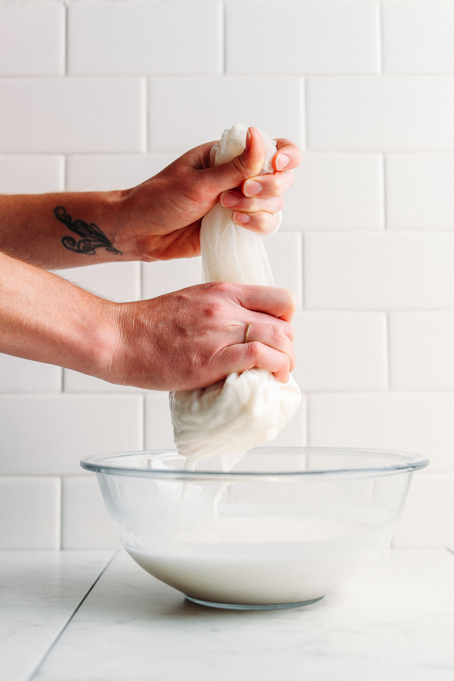 Straining homemade coconut milk through a nut milk bag into a large bowl